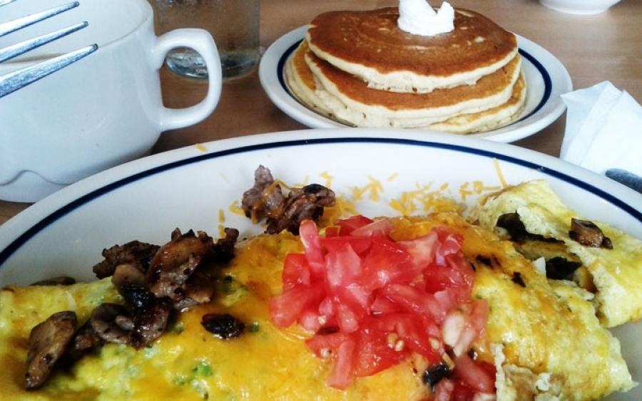 Omelette steak et champignons accompagnée d'une montagne de crêpes et d'un méga café